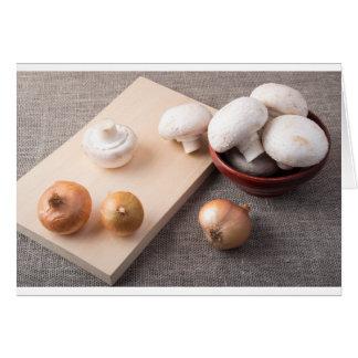 Ruwe champignonpaddestoelen en uien op de lijst wenskaart