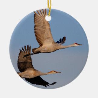 sandhill kranen tijdens de vlucht rond keramisch ornament