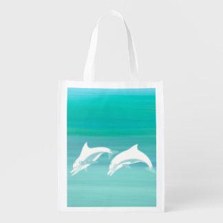 Speelse dolfijnen in aquamarijnoceaan boodschappentas