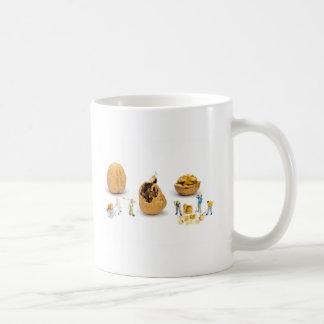 Team van miniatuurbeeldjes die okkernoot vervoeren koffiemok