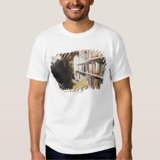 Tiener student in bibliotheek tshirts