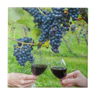 Twee handen die met rode wijn dichtbij blauwe keramisch tegeltje