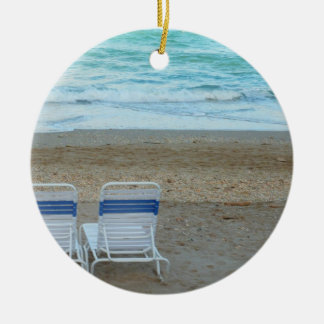 Twee stoelen op strand schuren oceaangolven rond keramisch ornament