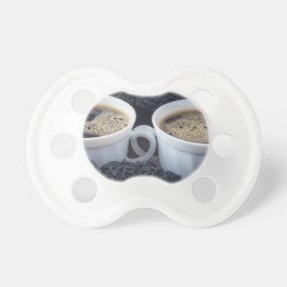 Twee witte koppen met zwart koffie en schuim baby speentje