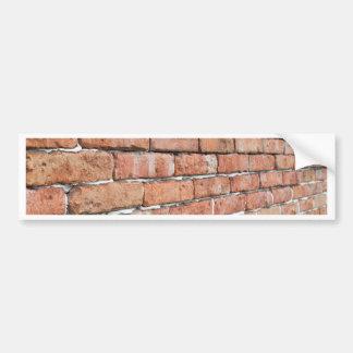 Uitzicht van een oude bakstenen muur met een bumpersticker