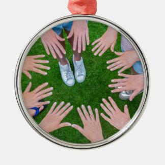Vele kinderenhanden die in cirkel boven gras zilverkleurig rond ornament