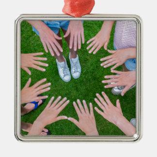 Vele kinderenhanden die in cirkel boven gras zilverkleurig vierkant ornament