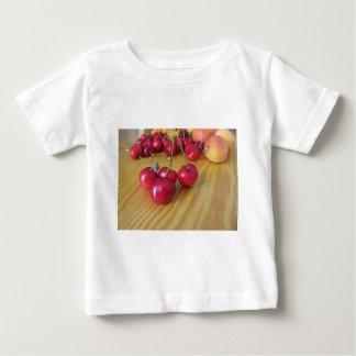 Verse de zomervruchten op lichte houten lijst baby t shirts