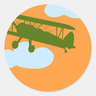 Vliegtuig op duidelijke oranje achtergrond ronde sticker