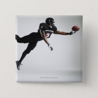 Voetbalster die in medio lucht aan vangstbal vierkante button 5,1 cm