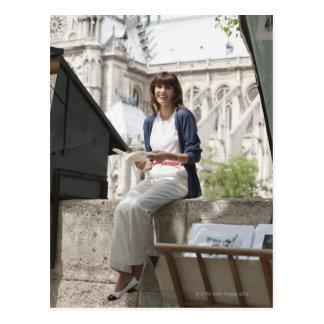Vrouw die een boek lezen bij een boekenstalletje, briefkaart