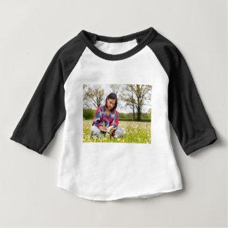 Vrouw die in weide met de lentebloemen schrijven baby t shirts