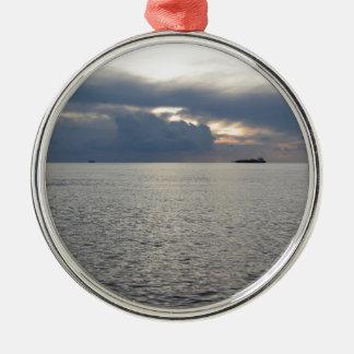 Warme zeezonsondergang met vrachtschip bij de zilverkleurig rond ornament