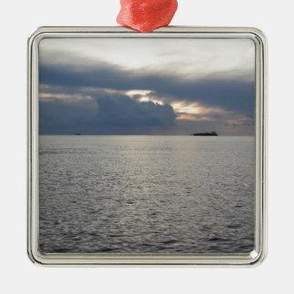 Warme zeezonsondergang met vrachtschip bij de zilverkleurig vierkant ornament