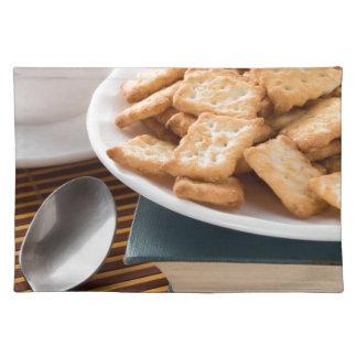 Wit bord met koekjes op het oude boek placemat