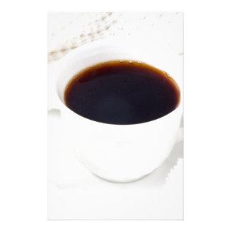 Witte kop met hete koffie en wollen briefpapier