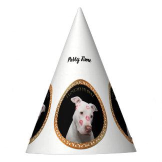 Witte pitbull met rode kussen helemaal over zijn feesthoedjes