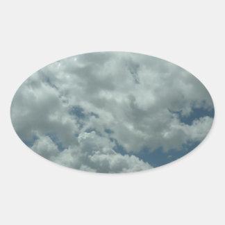 Witte, pluizige wolken in blauwe hemel ovale sticker