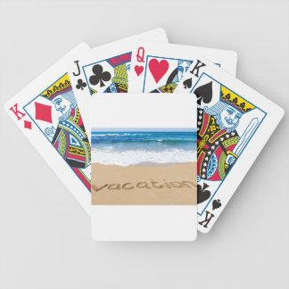 woord vakantie die op zandstrand op zee wordt poker kaarten